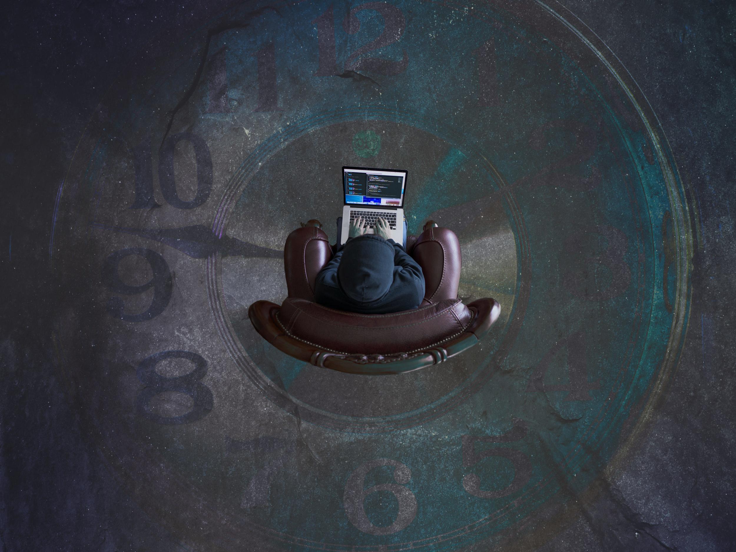 Mann in Sessel mit Laptop von oben in Uhrkreis