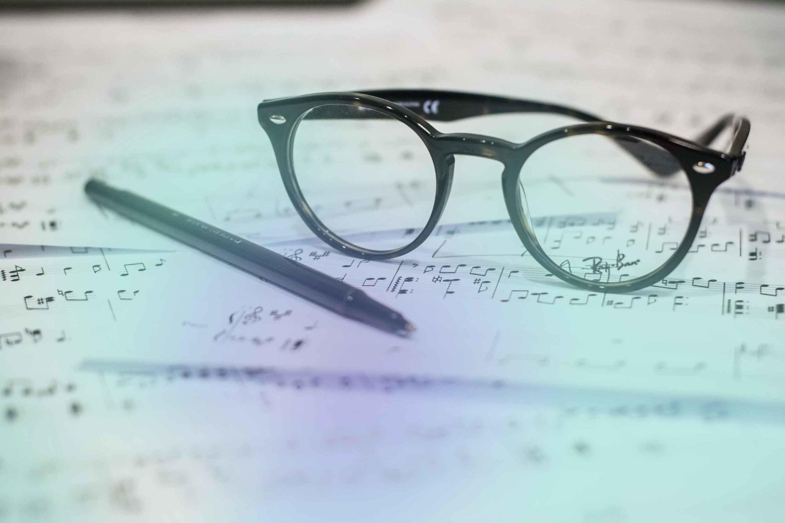 Brille und Stift auf Notenblättern