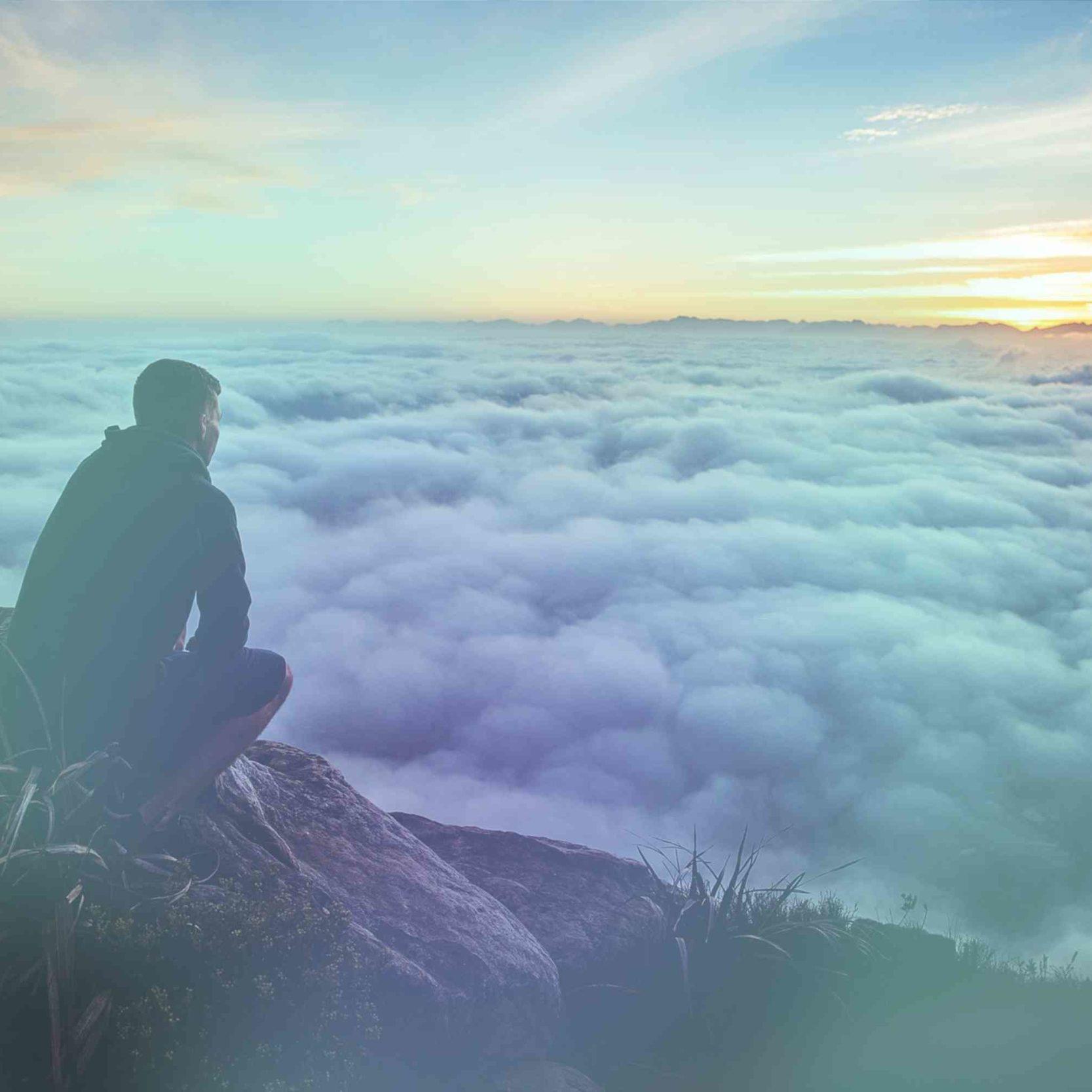 Man auf grauem Felsen blickt auf Wolken unter sich im Sonnenaufgang